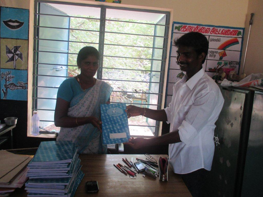 Panjertheerthi head master receiving noteboooks from MTI managining trustee Mani Rupakanthan